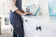 Mid section of young female baker at kitchen counter typing on laptop