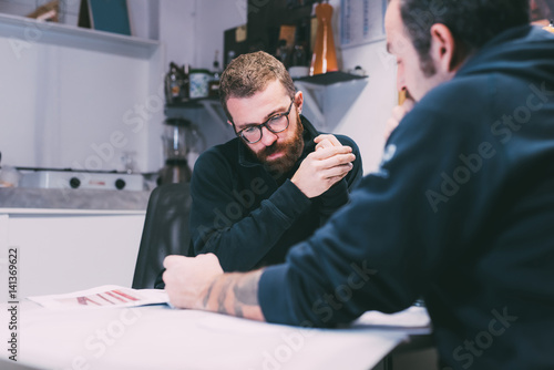 Two male metalworkers designing in forge office
