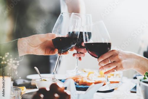 Plakat Szczęśliwi przyjaciele dopingujący z kieliszkami czerwonego wina w domu, radością i świętowaniem koncepcji, grupa ludzi robiących tosty i celebrująca rocznicę