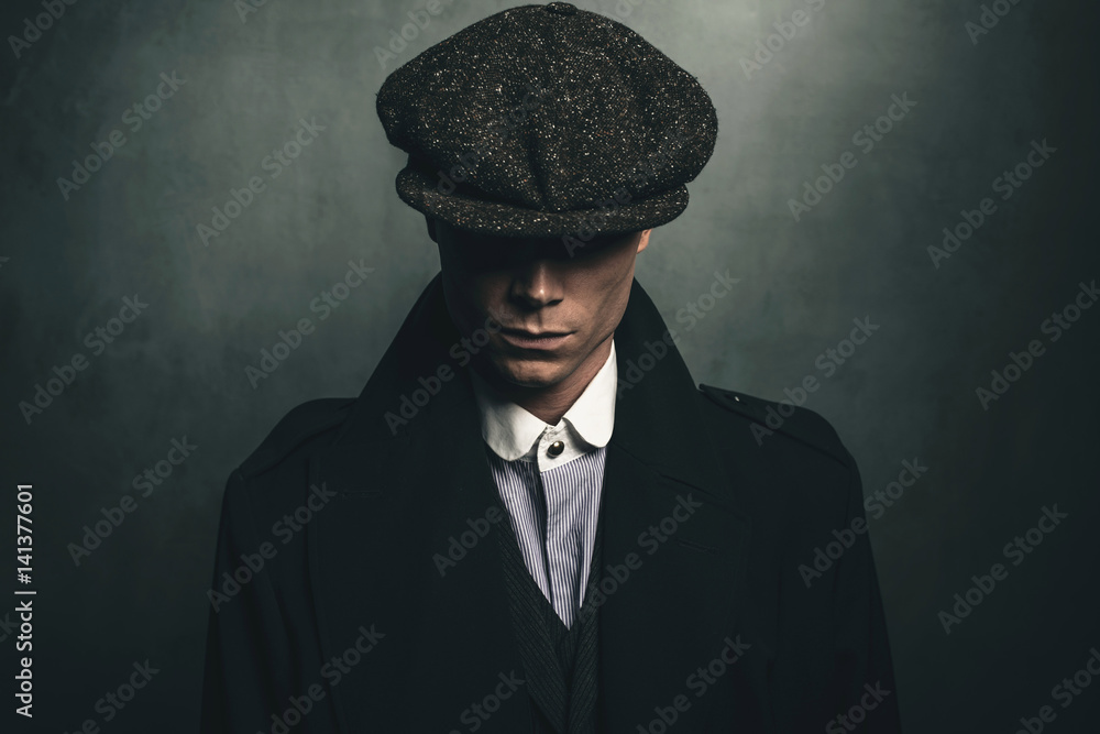 Fototapeta Mysterious portrait of retro 1920s english gangster with flat cap.