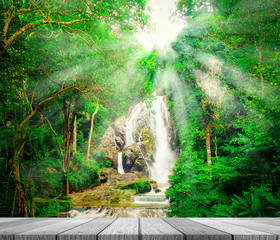 FototapetaWooden tabletop with waterfall in forest background