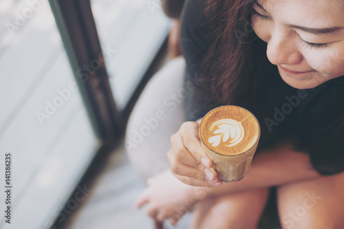 Fotografie, Obraz  Closeup image of Asian woman holding coffee cup and smelling hot coffee with fee