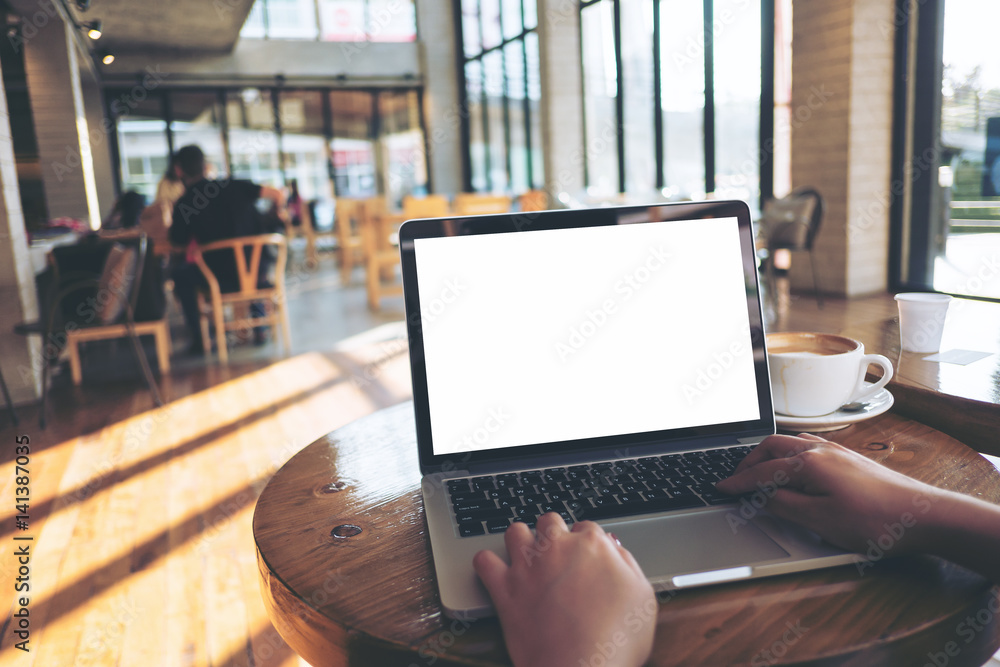 Fototapeta Mockup image of a woman using laptop with blank white screen on wooden table in modern loft cafe