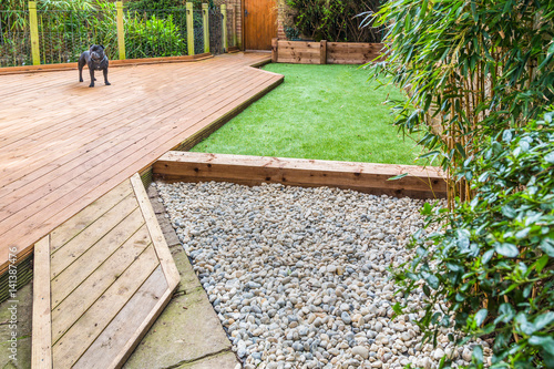 Foto op Aluminium Tuin A section of a residntial garden, yard with wooden decking, patio over a fish pond, a section of artificial grass and an area of stone pebble. There is a bamboo plant and a dog in the garden.