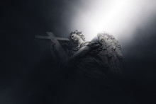 Angel With Cross Illuminated By A Beam Of Light