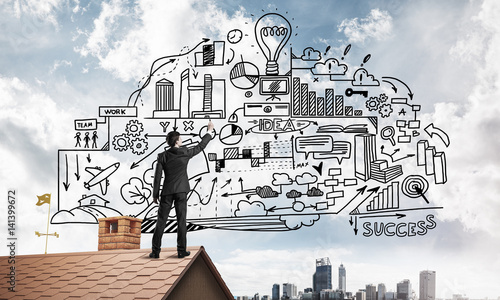Fototapety, obrazy: Rear view of businessman on house roof drawing his new business