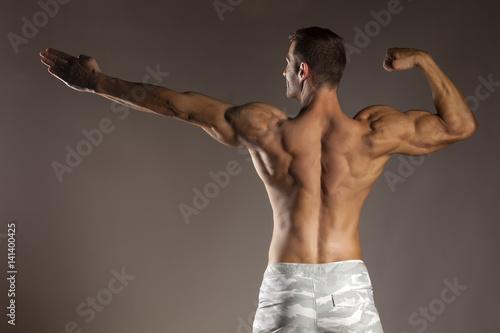 Zdjęcie XXL widok z tyłu półnaga przystojny i muskularny młody mężczyzna pozowanie na szarym tle