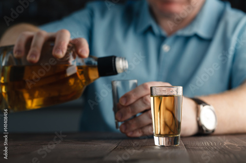 Tuinposter Bar Man is pouring tequila into glass