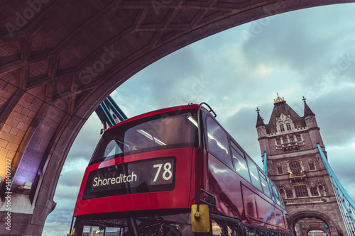 London iconic Tower Bridge and double decker red bus плакат