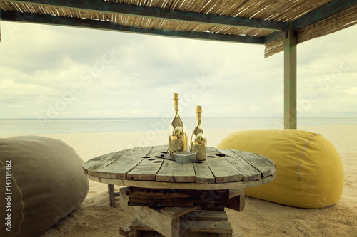 Two bottles of champagne on an old wooden table with pouf seats for romantic din Canvas Print