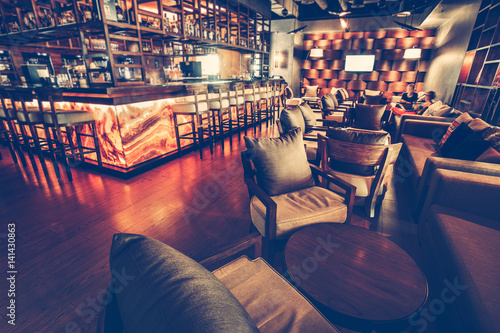Obraz A modern restaurant cafe interior with chair, table, sofa, lighting and bar decoration wall with alcohol ssortment. Concept of relaxing outside and communication. Vintage toning, dark lights - fototapety do salonu