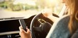 Cropped image of woman using smart phone while driving