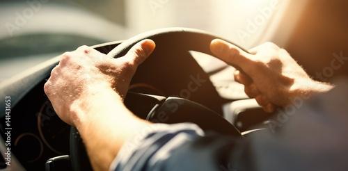 Cropped hands of man holding steering wheel Fototapet