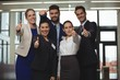 Successful businesspeople showing thumb up sign