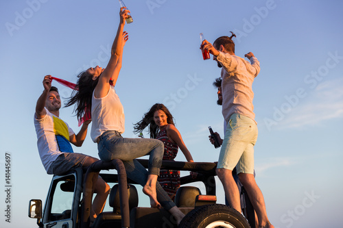 young group having fun on the beach and dancing in a convertible car