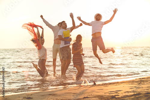 Fototapeta group of happy young people dancing at the beach on beautiful summer sunset obraz na płótnie
