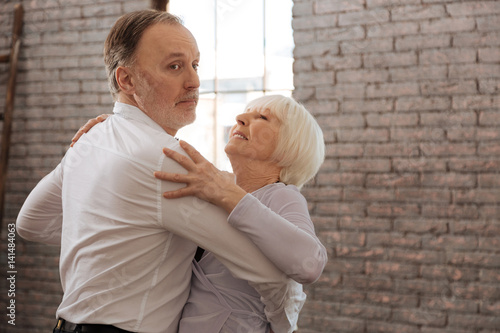 Fotografia Involved aged dance couple waltzing in the dance studio