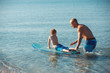 Young man teaching surfing his son in the ocean in a sunny day