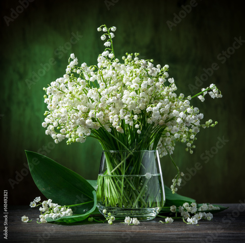 Lily of the valley bouquet on the wooden table.