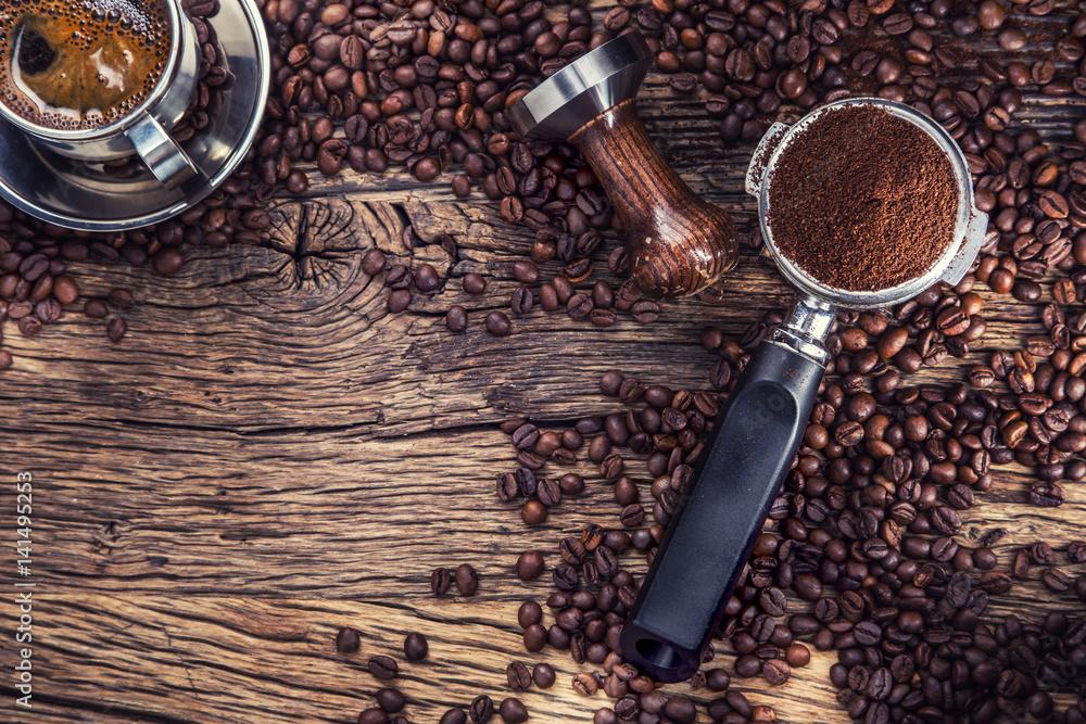 Fototapeta Coffee. Black coffee with coffee beans and portafilter on old oak wooden table.
