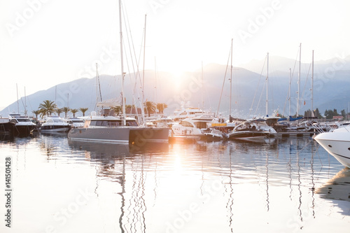 Yachts are preparing to sail in port at sunset on background of sea, mountains.