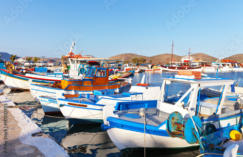 Poster Mediterraans Europa Greece. Crete. Traditional Cretan blue fishing boats on the pier in Elounda on a summer evening. Bright seascape