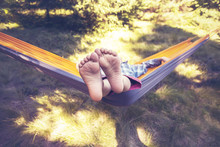 Kid Is Relaxing And Swinging In A Hammock