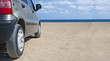 Passenger car on the sandy beach near the sea. Sunny blue sky Traveling and beach holidays concept. Copy space for text.