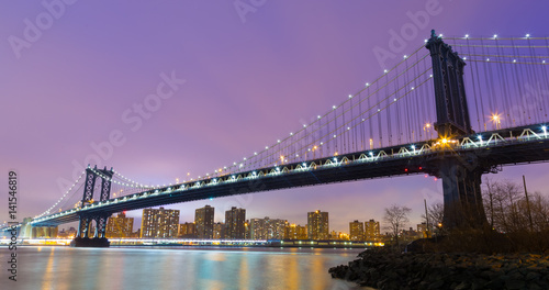 Manhattan bridge and New York City downtown skyline at dusk with skyscrapers illuminated over East River panorama. Copy space.