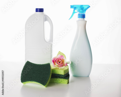 Fotografie, Obraz  A pink flower placed near the cleaning chemistry bottles and sponges