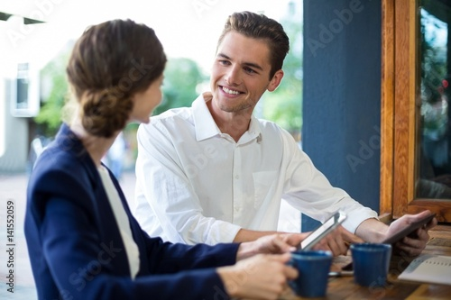 Fototapety, obrazy: Businessman and woman interacting while having coffee at counter