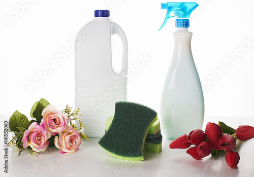Fotografie, Obraz  Small bunch of red and pink flowers placed near the cleaning chemistry bottles a