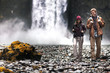 Couple hiking with backpacks and waterfall in background