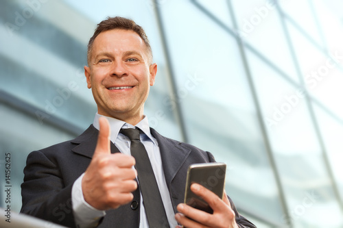 Fotografie, Obraz  Cheerful  businessman showing thumbs up and using cell phone