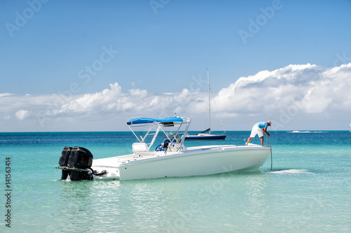 man, yachtsman on motorboat on water, in St. John, Antigua Fototapeta