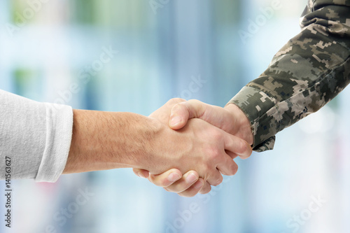 Fotografiet  Soldier and civilian shaking hands on white background, closeup