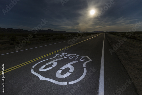 Photo Stands Route 66 Route 66 sign with full moon in the California Mojave desert.