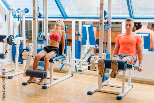 Spoed Foto op Canvas Fitness young friends working out in gym. saturated training of man and woman. Good results. Different exercises