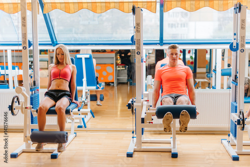 Spoed Foto op Canvas Fitness young friends working out in gym. saturated training of man and woman. Good results. Different dificult exercises