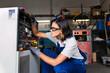 Female mechanic fixing a compressor engine