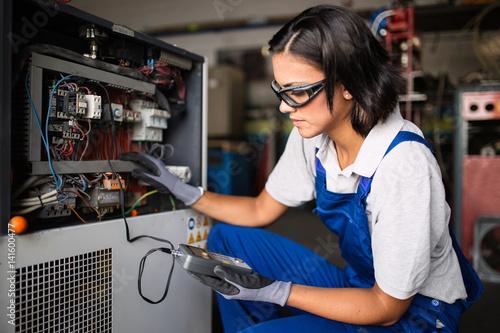 Papiers peints Akt Female mechanic fixing a compressor engine