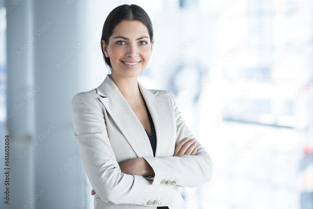 Fototapeta Smiling Pretty Business Woman With Arms Crossed