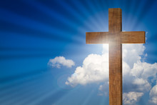 Jesus Cross On Blue Sky Background With Bright Light, Sun Rays, Clouds. Christian Wooden Cross. Easter Concept