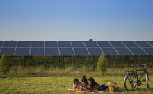 Three Girl Picnic In The Park. The Background Is A Solar Cell.