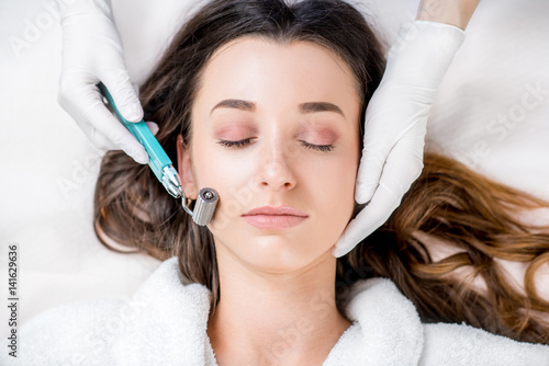 Fotografía  Making dry needlying procedure on woman's face in the cosmetology office