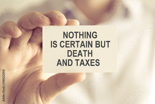 Fotografie, Tablou  Businessman holding NOTHING IS CERTAIN BUT DEATH AND TAXES message card