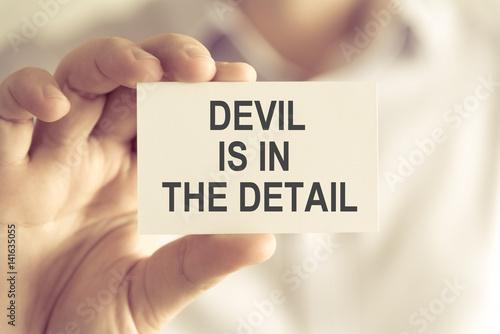 Fototapeta Businessman holding DEVIL IS IN THE DETAIL message card obraz