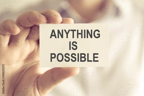 Valokuva  Businessman holding ANYTHING IS POSSIBLE message card
