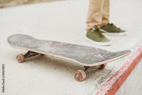 Close-up of skateboarders foot while skating in skate park Wallpaper Mural