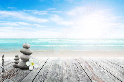 Photo  Stack of pebble stones and Plumeria at the beach on a wooden surface